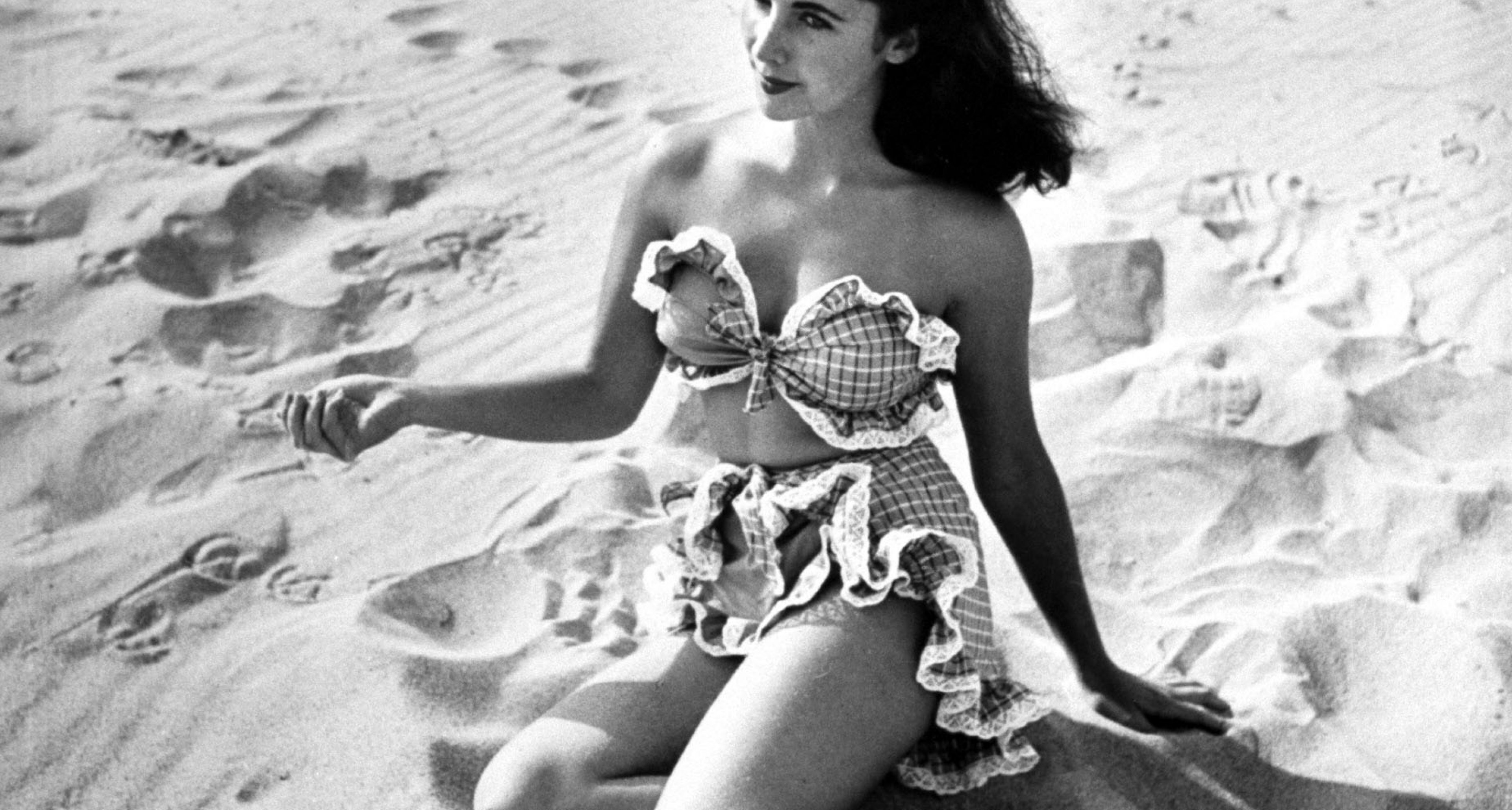 Actress Elizabeth Taylor, 15, showing off, frilly two-piece bathing suit on beach in 1947.