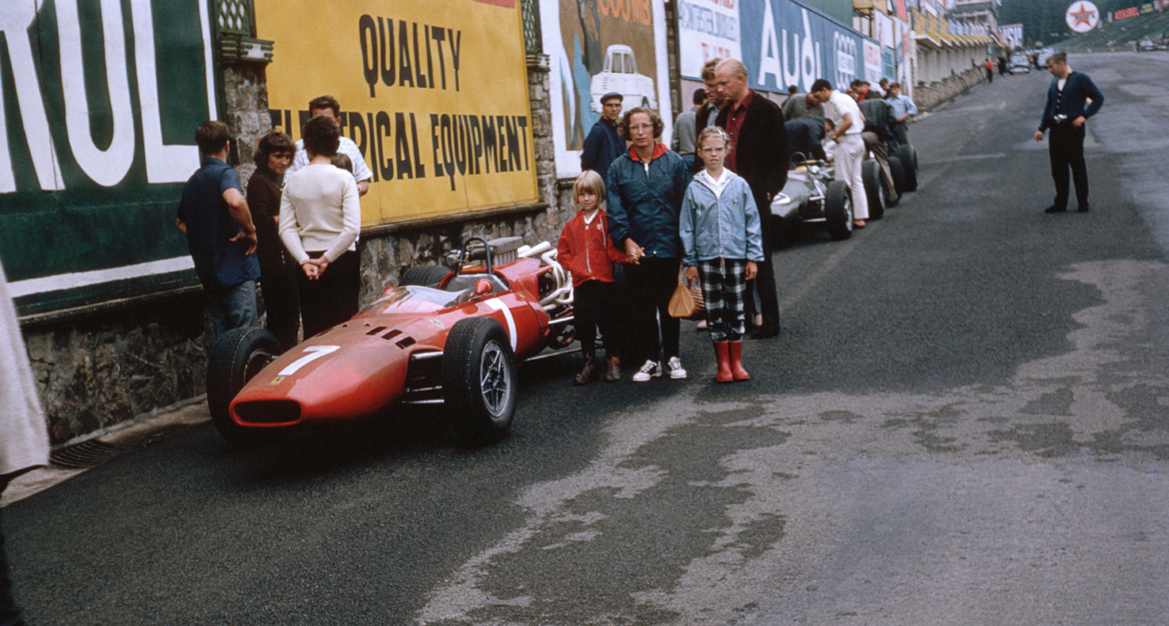 A belgian family poses for husband and father in front of Lorenzo Bandini's Ferrari 246 during the Belgian Grand Prix at Spa Francorchamps in 1966.