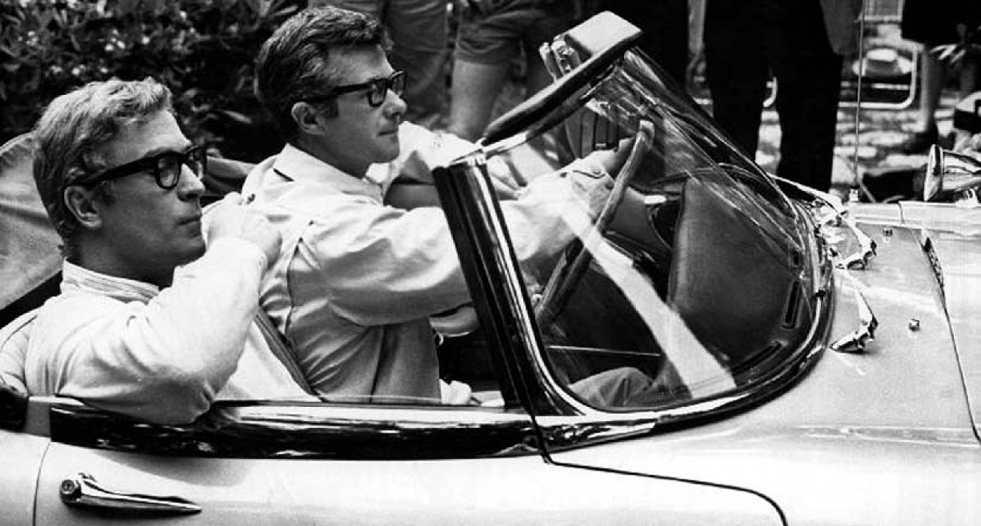 Michael Caine and director Bryan Forbes driving an E-type at the set of 'Deadfall' (1968).