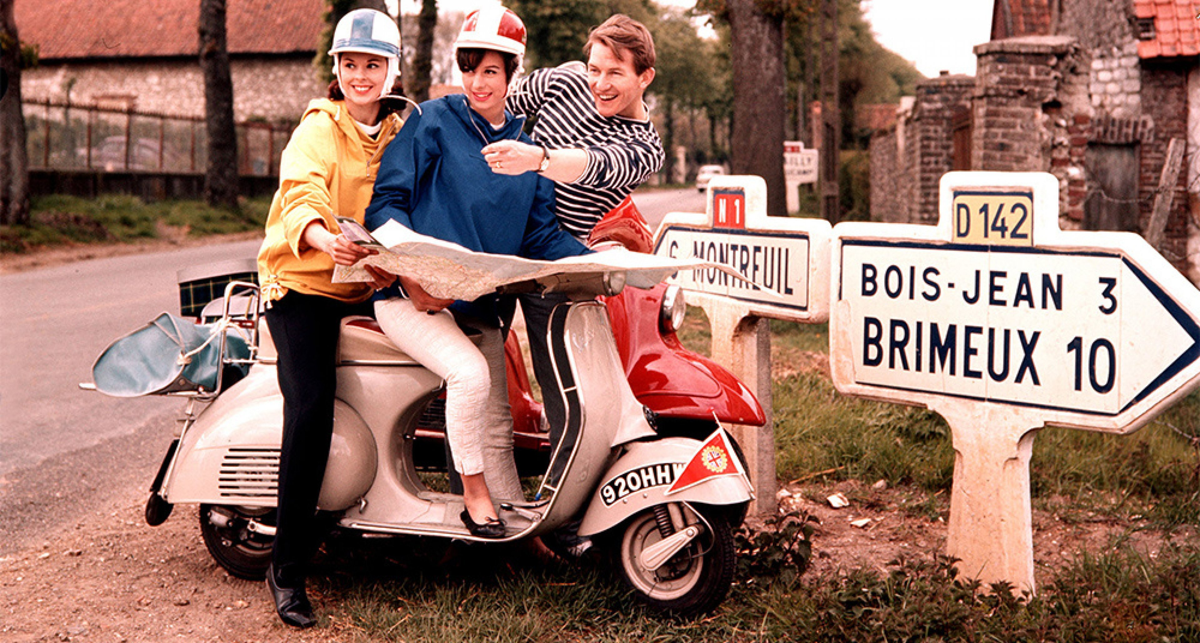 1960's, A couple astride a Vespa motorscooter ask for directions whilst touring France (Photo by Popperfoto/Getty Images)
