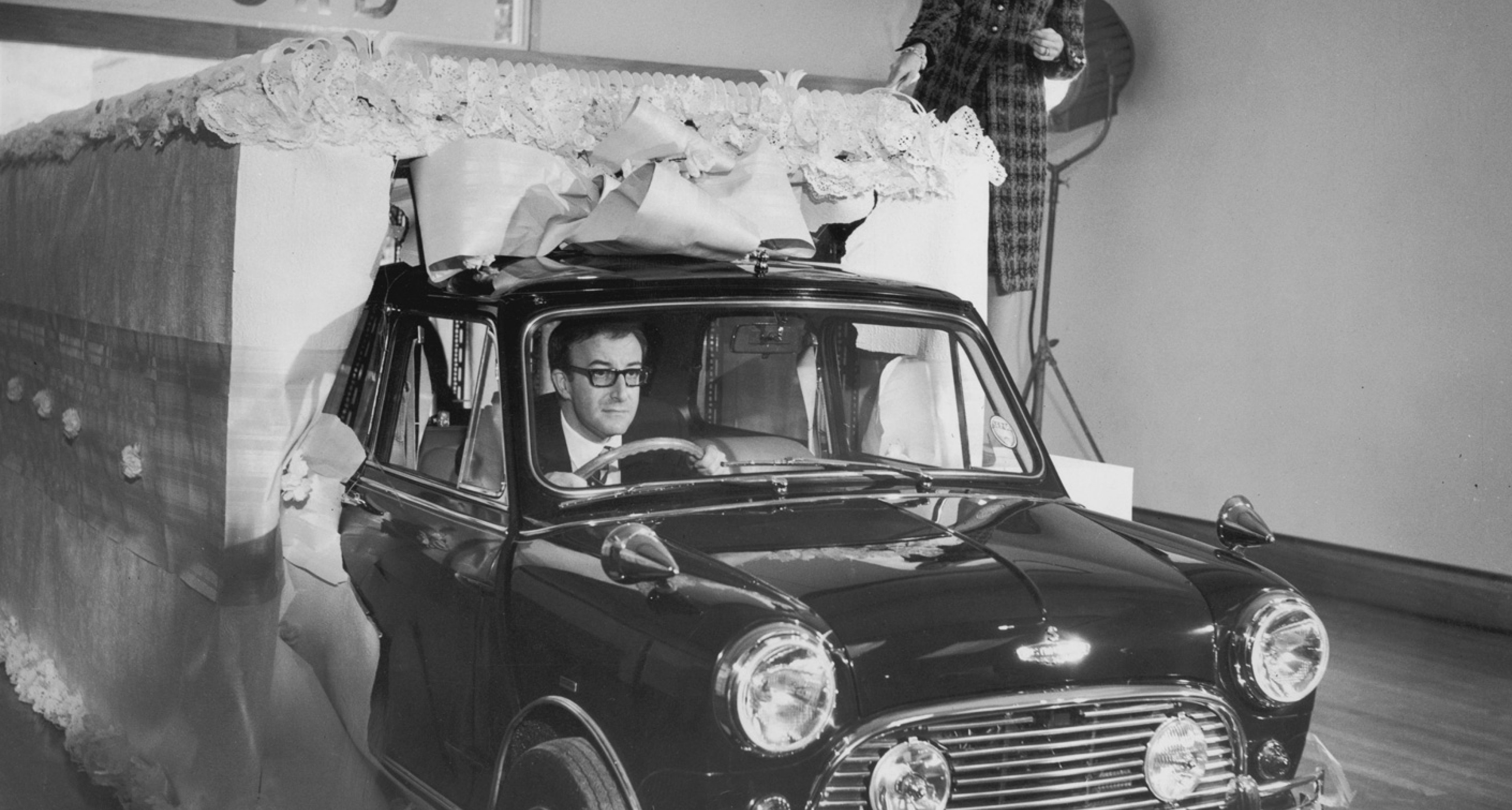 Sellers presents Britt Ekland (standing) with a Radford Mini
