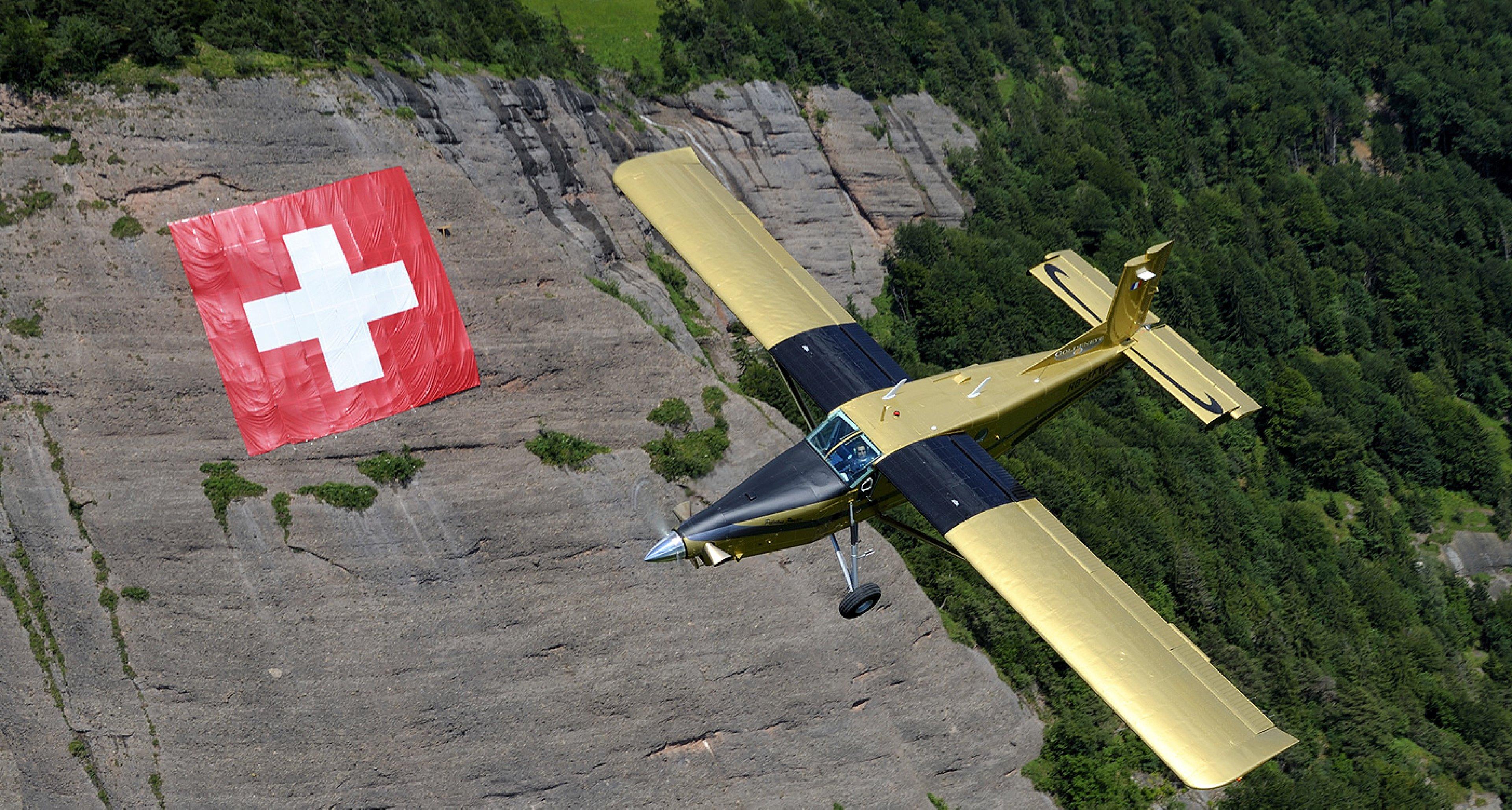 PC-6 'Goldeneye' flying over the Swiss flag